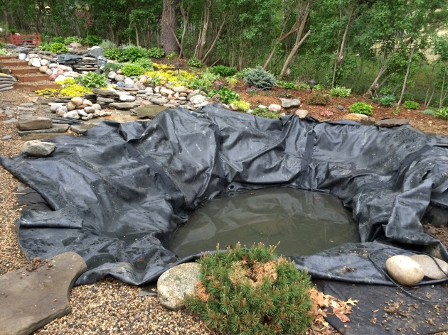 The lower pond has two tangential pond returns, taped down folds and is ready to fill once the filtration system is hooked up.