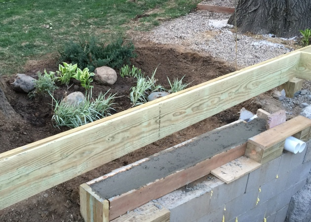 4.23.2016 We took down a giant dirt pile and replanted some hosta, grasses and a juniper. We poured a little concrete wall to keep the dirt out of the equipment pit.